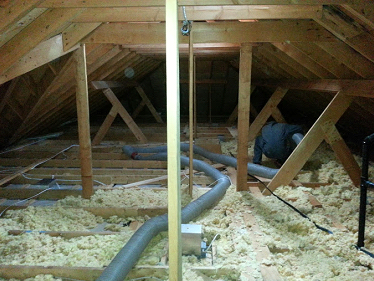Our technicians cleaning up damaged and soiled insulation in an attic